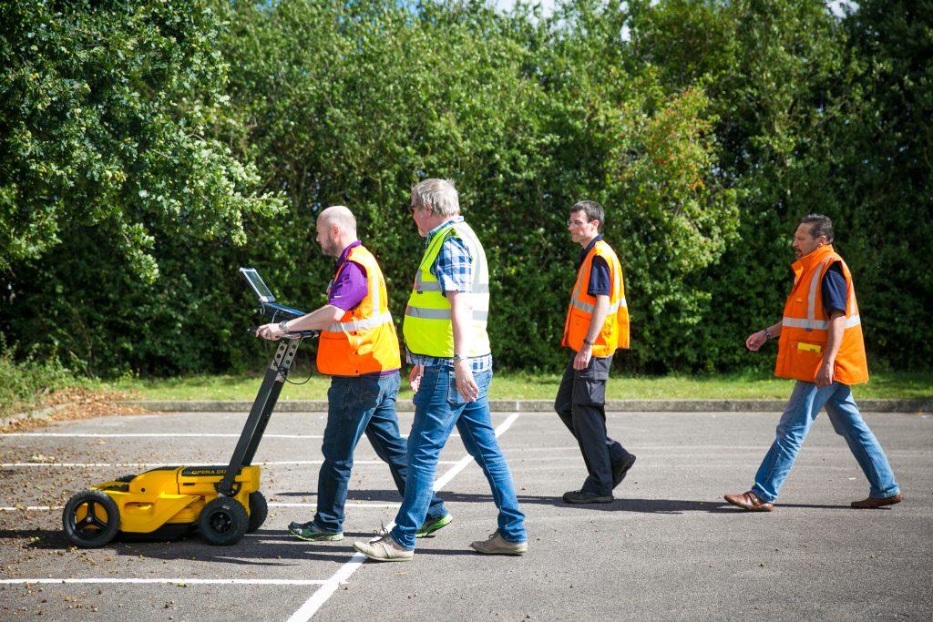 Men walking in hi vis with yellow machine